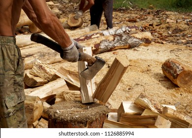 At the sawmill, the lumberjack, with strong and sunburnt hands, cuts wood with an ax.