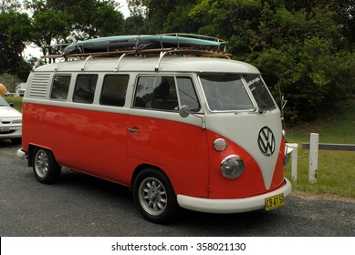 SAWTELL, AUSTRALIA, January 2, 2016: an orange Volkswagen campervan with a surf board on the roof is parked near the beach in Sawtell, New South Wales