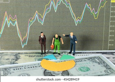 A sawyer is cutting the dividends for two business men. Conceptual image of dividends with stock chart and dollar background.