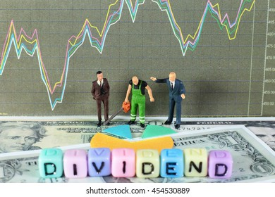 "A sawyer is cutting the dividends for two business men. Conceptual image of the word ""dividend"" with stock chart and dollar background."