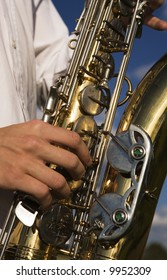 Saxophone being played outdoors under blue sky. Close up of brass and fingers.