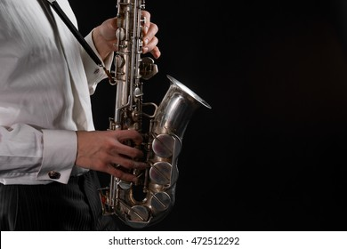 Saxophone in close up. Silver musical instrument in male hands with delicate fingers. Black background in studio.