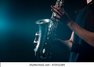 Saxophone in magical illumination. Musical instrument in male hands with visible veins. Nice silver sax for playing soul music.