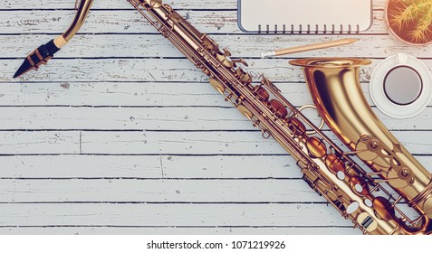 The saxophone is placed on a wooden floor, a cup of coffee and notebook is placed on the wooden floor.