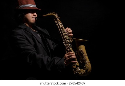 A saxophone player in a dark background