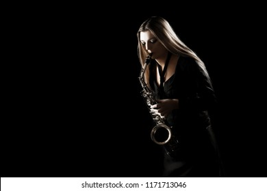 Saxophone player. Jazz musician saxophonist woman playing sax player isolated on black