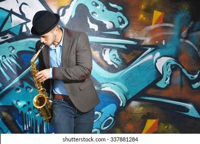 Saxophone player on graffiti wall background
