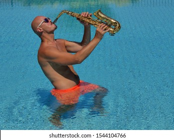 Saxophone player in orange swimming trunks stands waist-deep in water and plays the golden alto saxophone