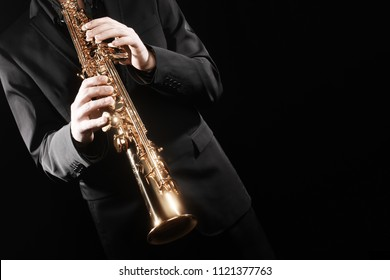 Saxophone player saxophonist playing soprano sax. Jazz music instrument hands closeup