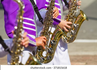 saxophone player in violet shirt in marching band