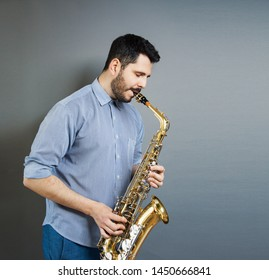 saxophone players on grey background. Saxophonist jazz man with Sax. Music concept.