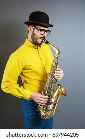 A saxophone players on grey background. Saxophonist jazz man with Sax. Leather Jacket dressed. Music concept. toned image