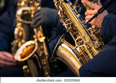Saxophones of a town band during a performance.