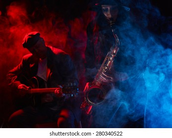 Saxophonistin, schöne junge Frau, rauchfreie Bühne und Gitarrist auf dem Hintergrund
