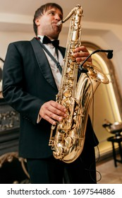 Saxophonist in a black suit plays music
