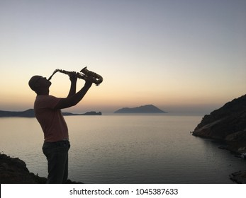Saxophonist in the evening by the sea on the mountain