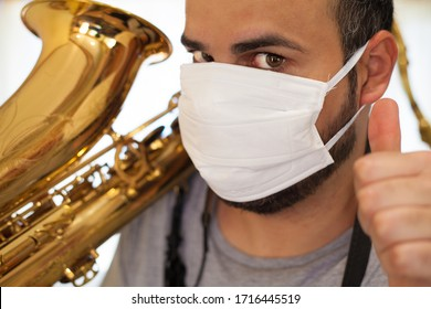 Saxophonist musician with mask protected from coronavirus with thumb upwards in an optimistic and positive signal