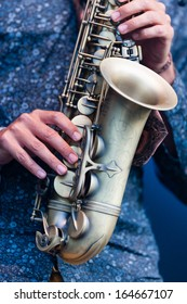Saxophonist playing a saxophone in an orchestra during a live performance, close up view of his hands manipulating the valves