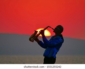 Saxophonist plays against the backdrop of a red sunset with a yellow big sun