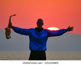 Saxophonist raised his hands to the sun amid stunning burgundy sunset and warm evening sun
