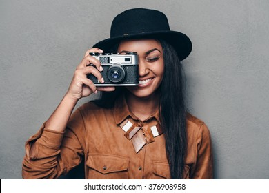 Say cheese! Beautiful cheerful young African woman holding retro styled camera and focusing on you with smile while standing against grey background