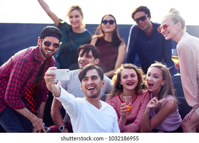 Say cheese. Joyful young friends enjoying the party while making selfies