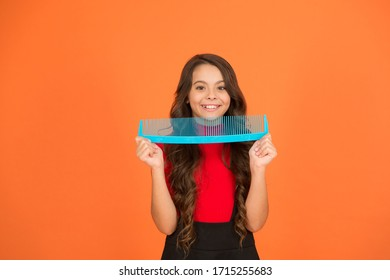 Say goodbye to knots and tangles. Happy child hold comb brown background. Hair combing. Combing before and after shampoo. Haircare and styling. Untangling or combing. Combing gives hair a flow.