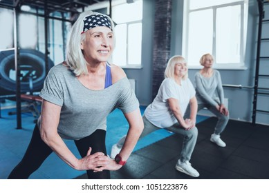 Say no to arthritis pain. Selective focus on a joyful woman smiling while lunging with a group of elderly ladies while all taking an exercise class at a fitness club.