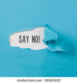 Say No message on torn blue paper revealing secret behind ripped opening.