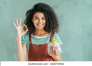 Say no to plastic, small steps to environmental concern. Mixed race woman in brown overalls and strip t-shirt use cotton bag for lemon, shows ok sign on green wall background. Zero waste concept.