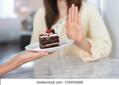 Say no to sweet during diet. Woman refusing to eat cake and push off.