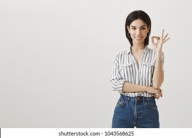 Say yes to new opportunities. Studio shot of beautiful dark-haired caucasian woman in stylish clothes showing okay or great gesture near face, smiling with approval, being pleased with new concept