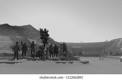 Sayanogorsk, Siberia, Russia - January 5, 2018: Sayano-Shushenskaya Dam in grey tones vintage style. Translation: Conquerors of the Yenisei. First builders of the Sayano Shushenskaya hydropower plant
