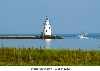 Saybrook Breakwater lighthouse guides fishing boat home in Connecticut. The tower is located at the end of a rocky breakwater.