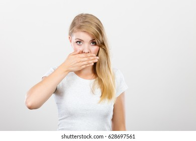 Saying bad things, shocking news concept. Ashamed young blonde woman having hand on her mouth. Studio shot on grey background.