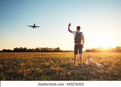 Saying hello at the sunset. Young man with his dog on the evening walk along the airport.