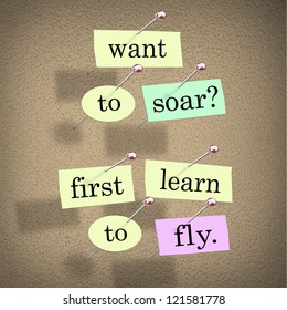 The saying Want to Soar, First Learn to Fly on pieces of paper pinned to a bulletin board, a motivational bit of advice to help you achieve success in life