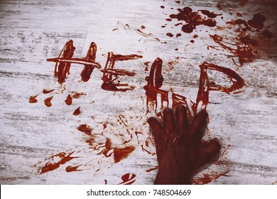 Says help, written in red blood on the dirty white floor of the bloody hand. The murder victim asks for help.