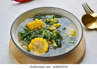 sayur bayam bening or spinach clear soup with corn  in grey bowl and wooden cutting board