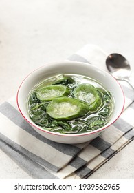 Sayur bening bayam dan gambas or  clear soup of spinach and luffa vegetables. Serve in white ceramics bowl. Selective focus