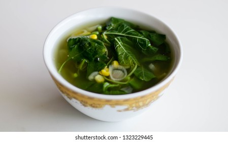 Sayur Bening Bayam or Spinach Clear Soup on white background. Boiled spinach with corn. Indonesian food.