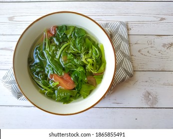 Sayur bening bayam or spinach clear soup is Indonesian food of spinach with tomatoes in bowl served on wooden white table. Selective focus. Copy space. Top view