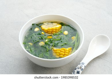 Sayur bening bayam or Spinach Soup is Indonesian food made from spinach and corn. Served on white bowl on grey table. Close up, selective focus.