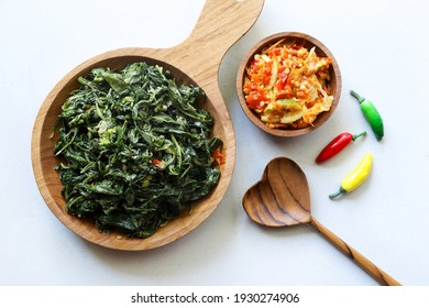 Sayur tumis daun singkong Cassava leaves stir fried and chili sauce served on a wooden plate on white background
