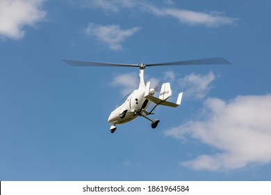 SAZENA, CZECH REP -July, 11, 2020. The two-seater gyroplane Calidus flies in the sky with clouds. in S?zena Airport in the Czech Republic.