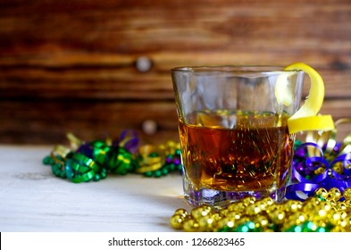A sazerac cocktail with a lemon twist in a rocks glass on a wooden table. Mardi gras decorations around. Wooden background.