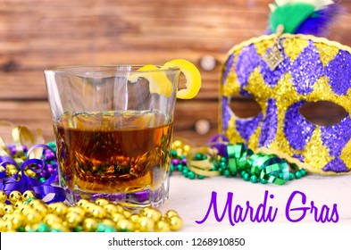 A sazerac cocktail with a lemon twist in a rocks glass on a wooden table. Mardi gras decorations around. Wooden background. Text added.