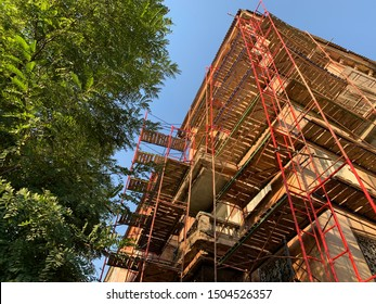 Scaffold before house. Reconstruction work using scaffolding. Composition for building company. Symbol of construction