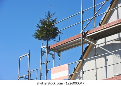 Scaffold with Fir Tree of the Topping Out Ceremony at the Front of a residential Building