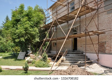 Scaffold on house during renovation. Building without construction workers.